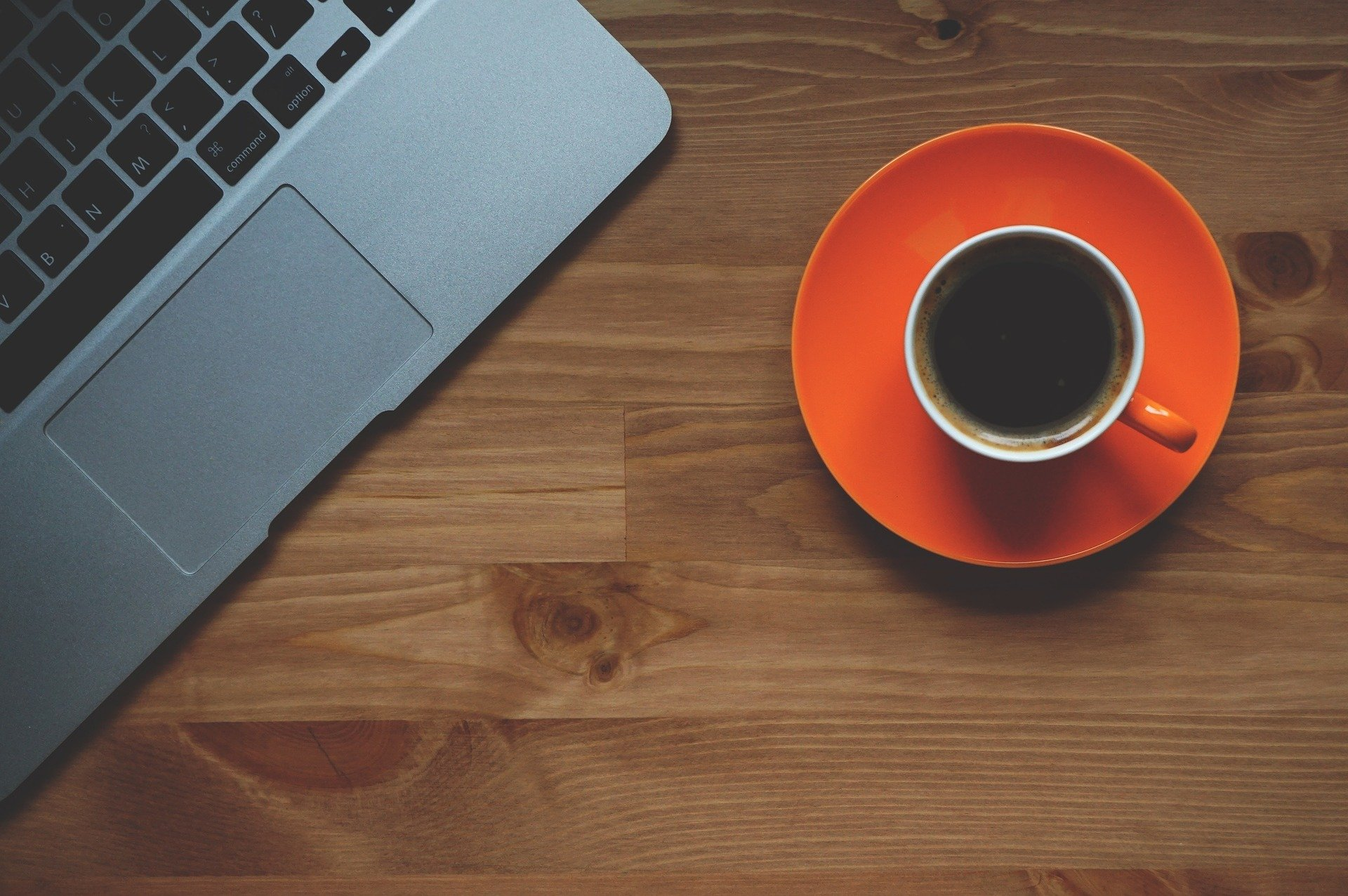 cup of black coffee sitting on orange coaster next to apple macbook on a wooden table